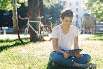 Souriante jeune femme assise sur la prairie à l'aide de tablette numérique — Photo de stock
