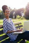 Portrait of young woman sitting on park bench using laptop — Stock Photo