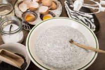Tigela de massa de bolo de semente de papoula na mesa de madeira — Fotografia de Stock