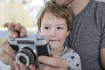 Father and son playing with camera — Stock Photo