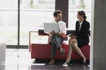 Kaufmann und Kauffrau im Büro Lobby sprechen — Stockfoto