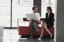 Businessman and businesswoman talking in office lobby — Stock Photo