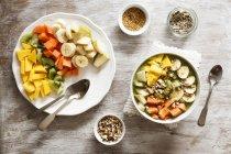 Smoothie bowl with mango, papaya, kiwi, banana, pear, lineseeds, sunflower-seeds and nuts — Stock Photo