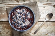Draufsicht der Smoothie Schüssel mit Heidelbeeren und Kokosflocken auf Holztisch — Stockfoto