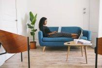 Empresária sentada no sofá no escritório usando laptop — Fotografia de Stock