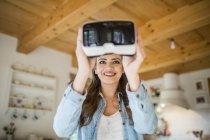 Young woman at home using Virtual Reality goggles — Stock Photo