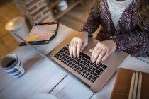 Mujer joven en casa trabajando con portátil - foto de stock