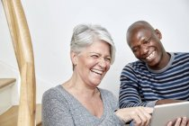 Portrait of laughing man and woman with digital tablet — Stock Photo