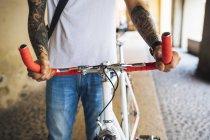 Junger Mann mit einem Fahrrad in der Stadt — Stockfoto