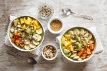 Les bols smoothie avec mangue, papaye, kiwi, banane, poire, lineseeds, tournesol-graines et noix — Photo de stock
