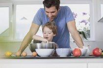 Батько і син, підготовка вафельний тісто кухні — стокове фото