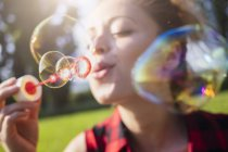 Woman blowing soap bubbles, close-up — Stock Photo