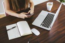 Donna che utilizza smartphone alla scrivania con laptop a casa — Foto stock