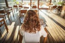 Giovane donna che utilizza notebook in caffè — Foto stock