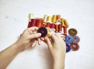 Frauenhände mit Nähutensilien auf weißem Hintergrund — Stockfoto
