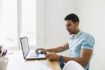Young man using laptop and smartphone in office — Stock Photo