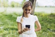 Smiling woman leaning against tree trunk looking at her smartphone — Stock Photo