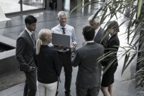 Selbstbewusste Geschäftsleute mit Laptop im Foyer — Stockfoto