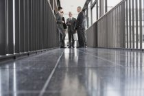 Group of caucasian businesspeople talking in hallway — Stock Photo
