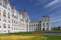 Hungary, Budapest, Parliament Building over green grass lawn — Stock Photo