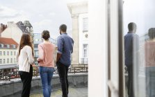 Man and two women standing on roof terrace — Stock Photo