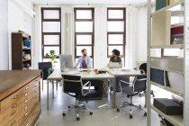 Dos profesionales creativos en la oficina - foto de stock