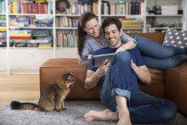 Взрослая пара лежит на диване, используя цифровой планшет — стоковое фото