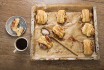 Baked Franzbroetchen on baking tray and cup of coffee on wooden table, elevated view — Stock Photo