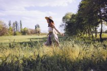 Young woman walking on a meadow in spring — Stock Photo