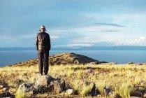 Перу, остров Амантани, человек, стоящий на вершине Пачамама с видом на Пачатату — стоковое фото