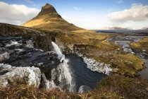Islande, péninsule de Snaefellsnes, Grundafjoerdur, Kirkjufell, cascade avec colline en arrière-plan pendant la journée — Photo de stock