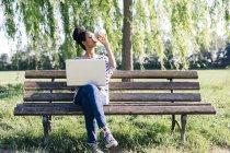 Jeune femme avec ordinateur portable assis sur un banc de parc de boire du café pour aller — Photo de stock