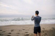 Jovem esportivo de pé com telefone celular na praia — Fotografia de Stock