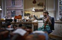 Скрипач лакирует отремонтированную скрипку в мастерской — стоковое фото