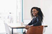 Giovane donna d'affari seduta alla scrivania in ufficio e sorridente alla fotocamera — Foto stock