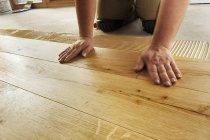 Uomo in posa di pavimenti in parquet di rovere finito, primo piano — Foto stock