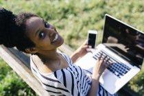 Retrato de mulher sorridente sentada no banco do parque usando laptop e smartphone — Fotografia de Stock
