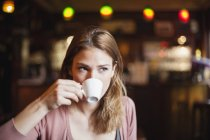 Portrait of young woman drinking cup of coffee in a cafe — Stock Photo