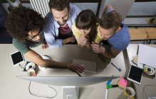 Team of creative professionals sitting around computer screen — Stock Photo