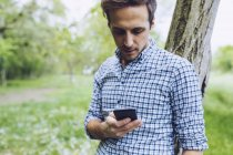 Man leaning against tree trunk looking at his smartphone — Stock Photo
