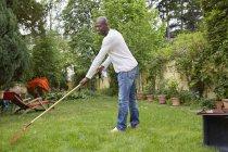 Чорна людина загрібати на галявині в саду — стокове фото