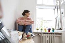 Nachdenkliche Frau sitzt am Fenster und schaut hinaus — Stockfoto