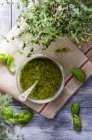 Pesto di basilico in un bicchiere e foglie verdi fresche su asciugapiatti, vista dall'alto — Foto stock