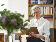 Retrato de mujer mayor sonriente con tableta digital en casa - foto de stock