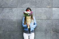 Молодая женщина держит букет цветов перед лицом к серой стене — стоковое фото