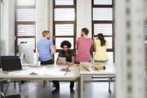 Team di professionisti creativi seduti alla scrivania in ufficio — Foto stock