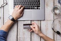 Mann sitzt am Schreibtisch und bezahlt online mit Kreditkarte — Stockfoto