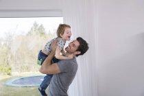 Buon padre che solleva ridendo figlio — Foto stock