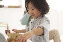 Wenig asiatische Mädchen spielen mit Ihr Holz Spielzeug — Stockfoto