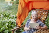 Жінка сидить газону стільці, використовуючи цифровий планшетний — стокове фото